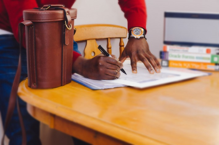 man writing on desk with books